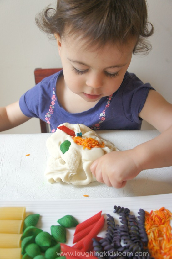 pressing playdough with pasta