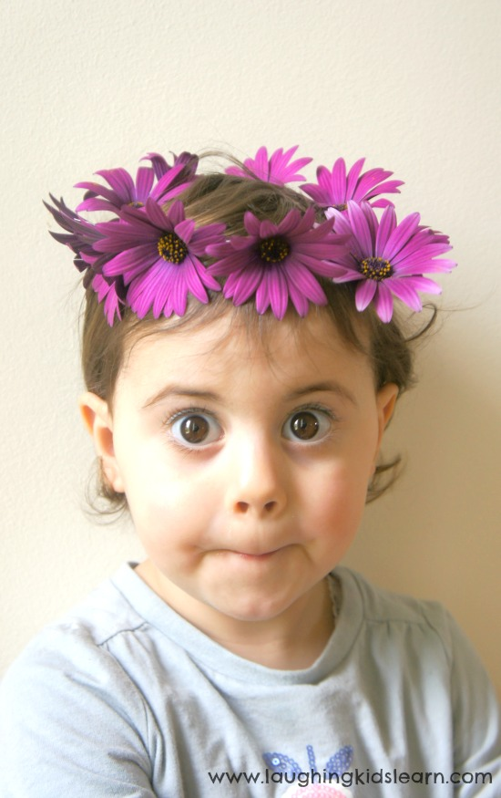 Toddler pulling a funny face with a daisy chain headpiece