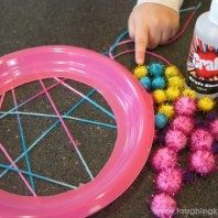 Plate dreamcatcher craft using pompoms from The Reject Shop