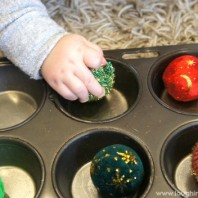Baby playing with sensory balls on tray