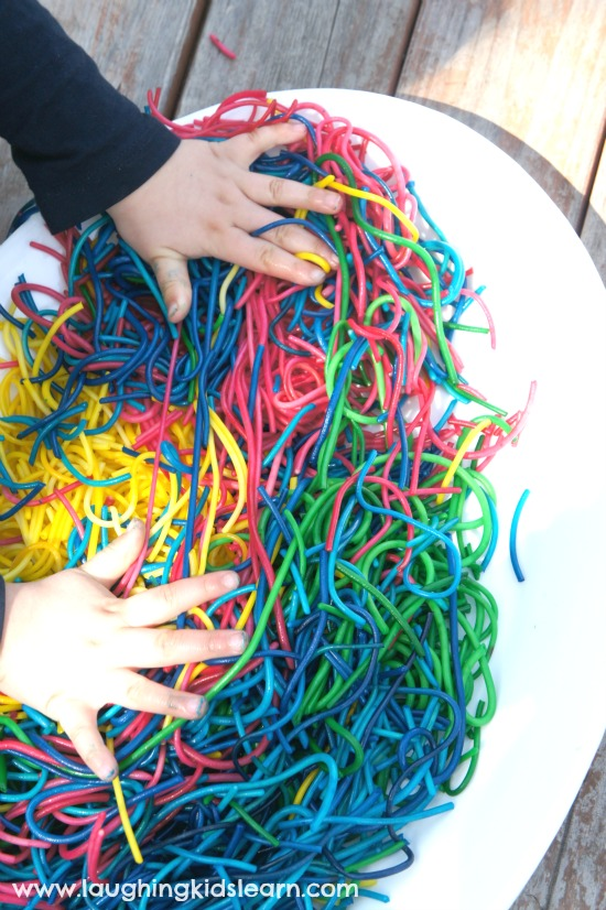 Mixing spaghetti during sensory play