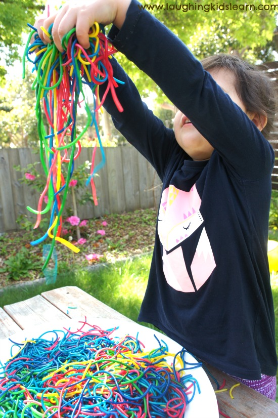 Playing with sensory spaghetti in rainbow colours