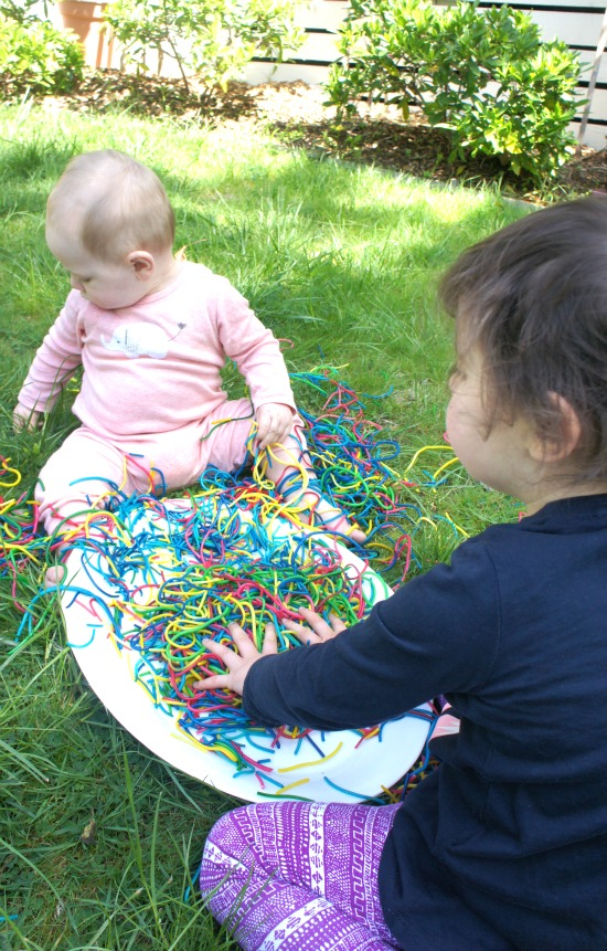 Toddler and baby playing together with spaghetti