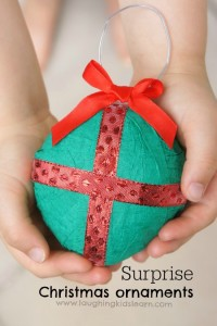 Hands holding surprise Christmas ornament with gift inside