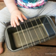 baby musical guitar instrument that is homemade and kids can enjoy playing. Just use a baking tin and rubber bands.