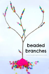 Threading pony beads on tree branches to build fine motor skills