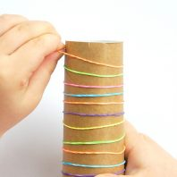 simple fine motor activity using a cardboard tube and elastic bands