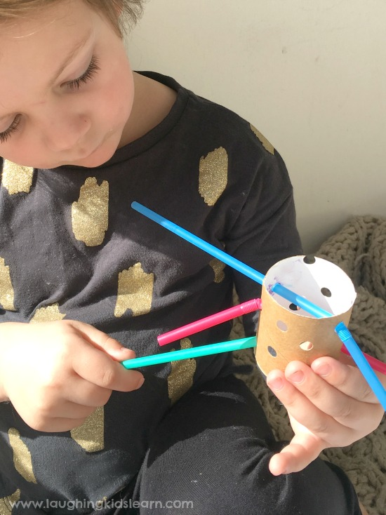 using fine motor skills for threading straws in cardboard tube