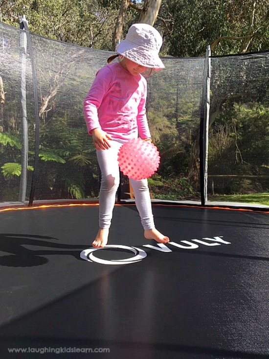 Playing and jumping on a Vuly trampoline for kids. Using balls. #vuly #vulytrampoline #trampolineforchristmas #sponsored #gifted #ad #bounce #trampolineideas #funonatrampoline #gamesfortrampoline #christmasideas #familygames #funforthefamily #toddlerplayideas #toddlers #preschoolers #vulyaustralia #australia #funforkids #learnwithplay #funathome