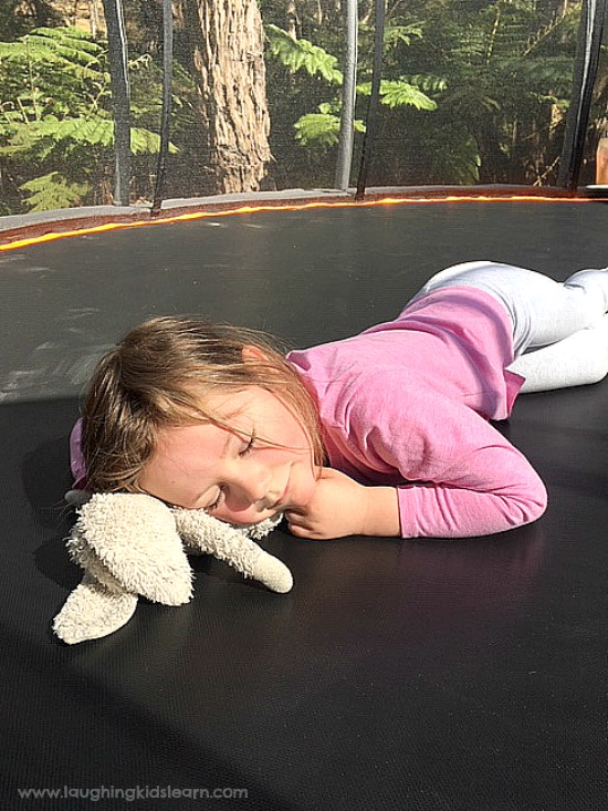 Toddler or preschooler enjoying and resting on trampoline. Lots of fun for the whole family. #vuly #vulytrampoline #trampolineforchristmas #sponsored #gifted #ad #bounce #trampolineideas #funonatrampoline #gamesfortrampoline #christmasideas #familygames #funforthefamily #toddlerplayideas #toddlers #preschoolers #vulyaustralia #australia #funforkids #learnwithplay #funathome