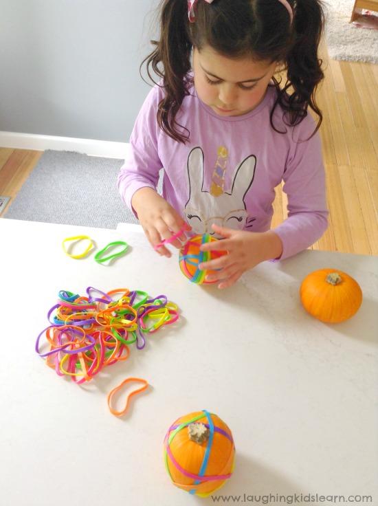 School child putting elastic bands over pumpkins #finemotorskills #finemotor #finemotoractivities #halloween #happyhalloween #kidshalloween #halloweenactivities #halloweenplayideas #minipumpkins #elasticbands #earlyyears #funathome #homeschool #preschool #preschooler #toddlers #toddlerplayideas #simpleplayideas #easyplayideas #playmatters #kbn #ots #ot #otactivities #lovetolearn