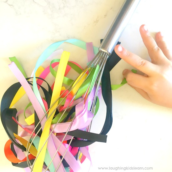 Ribbon and whisk fine motor activity for kids is fun and great. #finemotor #finemotorskills #ribbons #lovetoplay #simpleplayideasforkids #indooractivities #babyplay #babyplayideas #homeschooling #homeschool #lovetolearn #preschool #playgroup #playtime #mothersgroup