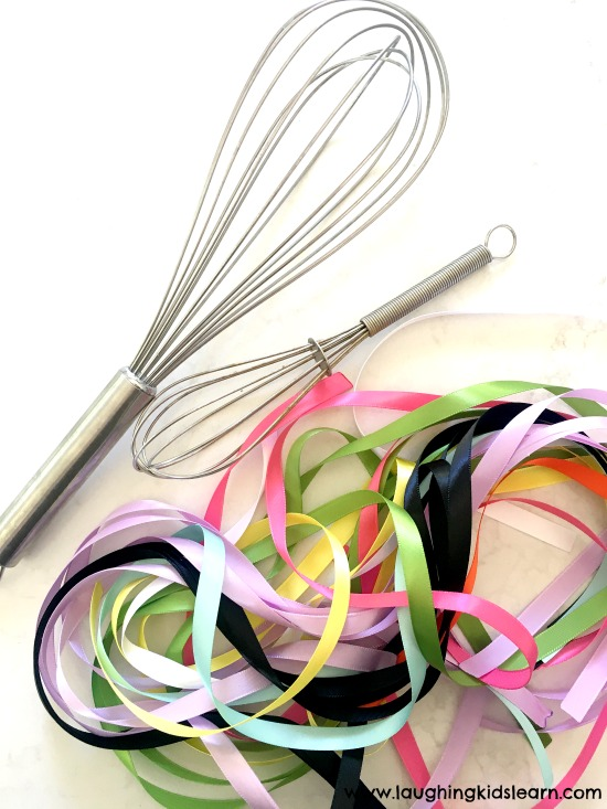 not pompoms and whisk, but ribbons and a whisk for your child to pull at and remove. Ribbon and whisk fine motor activity for kids is fun and great. #finemotor #finemotorskills #ribbons #lovetoplay #simpleplayideasforkids #indooractivities #babyplay #babyplayideas #homeschooling #homeschool #lovetolearn #preschool #playgroup #playtime #mothersgroup