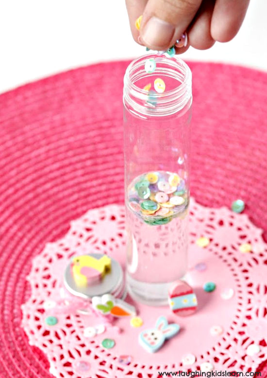 Filling up waster themed sensory bottles for children as a great alternative to chocolate. Very calming. #sensorybottles #eastergiftidea #eastergiftideas #sensoryplay #eastertheme #calminggifts